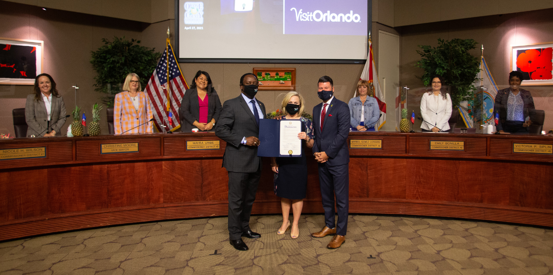 Foreground, from left to right: Mayor Jerry Demings; Casandra Matej, President and CEO of Visit Orlando; Robert Agrusa of the Central Florida Hotel & Lodging Association